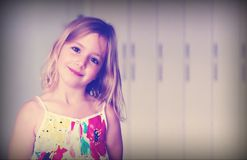 Sex åriga blonda flicka i en vit klänning för sommar med blommor som ler på en abstrakt bakgrund med blå dimmaeffekt Arkivfoto