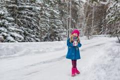 Sex åriga flicka i ett blått lag och en rosa hatt och kängor som grimacing i vinterskogen Royaltyfri Foto