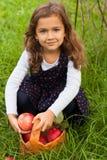 Sex årsflickahåll i hennes hand nya mogna röda Apple i sommargummin Arkivbilder