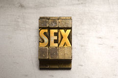 Sex. Brass / Gold colored Sex on silver metal background royalty free stock photos