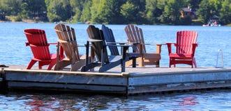 Sex Adirondack stolar på skeppsdockan Fotografering för Bildbyråer