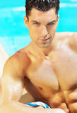 Sex appeal. Sexy shirtless handsome male model with sparkling blue eyes against blue swimming pool background Stock Image