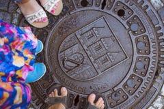 Sex ben tre personer står på den våta gjutjärnmanhålet, Prague Arkivbilder