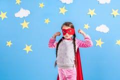 Sex blonda flicka för år klädde som superheroen som har gyckel hemma Unge på bakgrunden av den ljusa blåa väggen Royaltyfri Fotografi