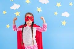Sex blonda flicka för år klädde som superheroen som har gyckel hemma Unge på bakgrunden av den ljusa blåa väggen Royaltyfri Bild