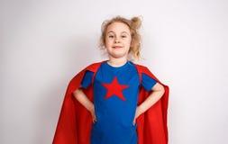 Sex blonda flicka för år klädde som superheroen som har gyckel hemma Vit vägg på bakgrund Arkivfoto
