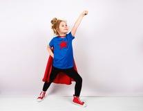 Sex blonda flicka för år klädde som superheroen som har gyckel hemma Vit vägg på bakgrund Arkivfoton