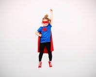 Sex blonda flicka för år klädde som superheroen som har gyckel hemma Vit vägg på bakgrund Royaltyfria Bilder