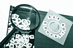 Sex education. Concept with key words and condom on game board Royalty Free Stock Image