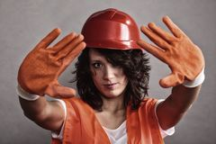 Sexy girl in safety helmet showing stop sign. Sex equality and feminism. Sexy girl construction worker builder in orange vest and hard hat showing stop sign hand Stock Photo