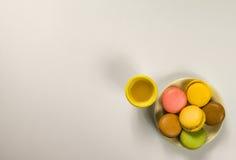 Sex färgade makron på en platta med orange fruktsaft Arkivbild