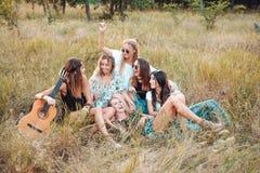 Sex flickor i natur sitter på gräset Arkivbild