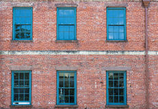 Sex gröna Windows på gammal tegelstenbyggnad Arkivbild