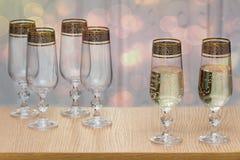 Sex härliga glass vinexponeringsglas, två fyllde med champagne Arkivbilder