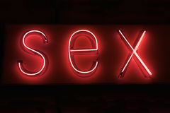 SEX hot red neon on black background. Close-up of the word SEX is spelled out in hot red neon sign against a black background Stock Photography