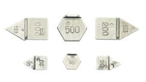 Sex knappar som är ordnade från tio lilla kalibreringsvikter Arkivfoton