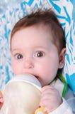 Sex-månad flickadrinkar mjölkar från en flaska Arkivbilder