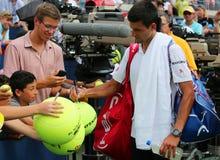 Sex Novak Djokovic för mästare för storslagen Slam för tider undertecknande autografer efter match för US Open 2014 Royaltyfria Bilder