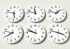 Sex parallella klockor på väggen som visar världstid arkivbilder