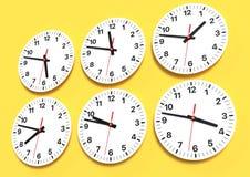 Sex parallella klockor på väggen som visar världstid arkivfoton