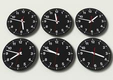 Sex parallella klockor p? v?ggen som visar v?rldstid arkivfoto