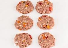 Sex rå hamburgare som göras pre på vit bakgrund Fotografering för Bildbyråer