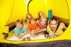 Sex roliga barn som lägger i tältet Arkivfoton