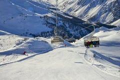 Sex-Seat Ñ hairlift lyfter bergskidåkarefamiljen på kullen i Tyrol fjällängar arkivfoto