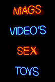 Sex shop neon sign. Blue and red neon sign of the words 'Mags videos sex toys' on a black background stock image