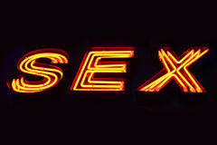 Sex shop neon sign. Close-up over black background Stock Image