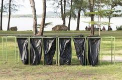Sex svarta avskrädepåsar på parkera Arkivfoton