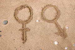Sex symbols. Drawing on the sand - Sex symbols Royalty Free Stock Images