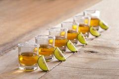 Sex tequilaskott i rad med limefruktskivan och saltar arkivbild
