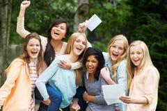 Sex tonårs- flickor som firar lyckade examenresultat royaltyfri fotografi