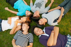 Sex tonårs- vänner som ligger på gräset Arkivbild