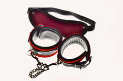 Sex toys. Red leather handcuffs and bandage for eyes Stock Photos