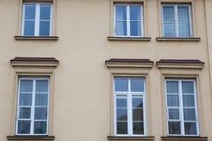 Sex vit Windows på fasaden av ett nytt beige hus royaltyfri bild