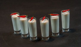 Sex vitkokosnötdrinkar dekorerade med röda peppar, alla på en bl Royaltyfri Fotografi