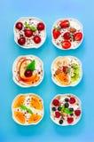 Sex yoghurter med nya frukter och bär Arkivbild