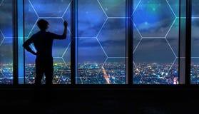 Sexhörningsraster med mannen vid stora fönster på natten arkivfoton