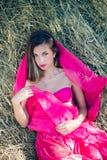 Sexi die jonge dame met lang haar in roze verbazen Royalty-vrije Stock Afbeeldingen
