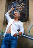 Sexi Man in a white shirt and ornamental window on background. A Stock Photos