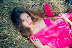 Sexi pensive young lady with long hair in pink Royalty Free Stock Photography