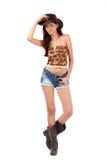 Sexig amerikansk cowgirl med kortslutningar och kängor och en cowboyhatt. Royaltyfri Foto