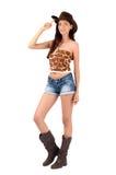 Sexig amerikansk cowgirl med kortslutningar och kängor och en cowboyhatt. Royaltyfri Bild