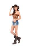Sexig amerikansk cowgirl med kortslutningar och kängor och en cowboyhatt. Arkivbild