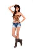 Sexig amerikansk cowgirl med kortslutningar och kängor och en cowboyhatt. Arkivfoton