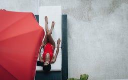 Sexig asiatisk kvinna i en r?d baddr?kt som l?gger, i sunbed p? poolsiden royaltyfri foto
