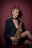 Sexig attraktiv kvinna med saxofonen som poserar på röd bakgrund Ung sinnlig blond spela saxofon Musikinstrument jazz Arkivbilder