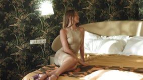 Sexig barnmodell som poserar att ligga på en säng i en beige klänning och på höga häl stock video
